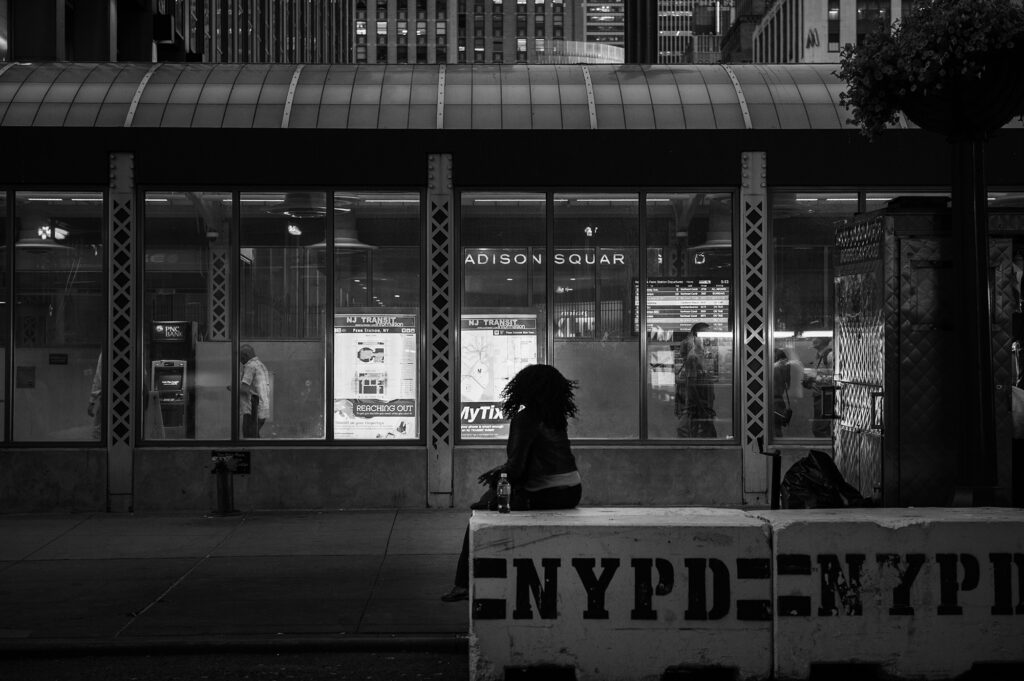 Woman sitting on a concrete barrier in NY - Alessandro Cancian Photography